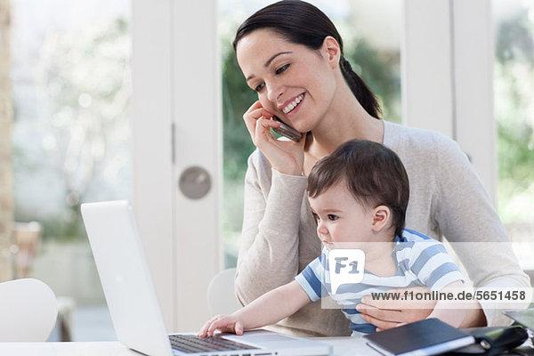 Mutter auf dem Handy und Baby beim Blick auf den Laptop