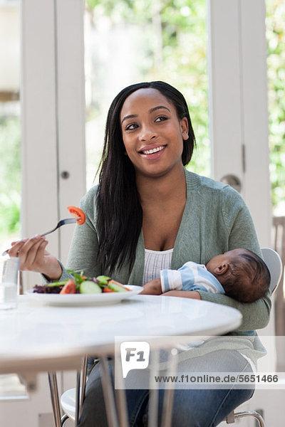 Mutter hält Baby-Sohn und Mittagessen