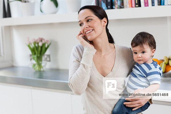 Mutter auf dem Handy  hält Baby Sohn