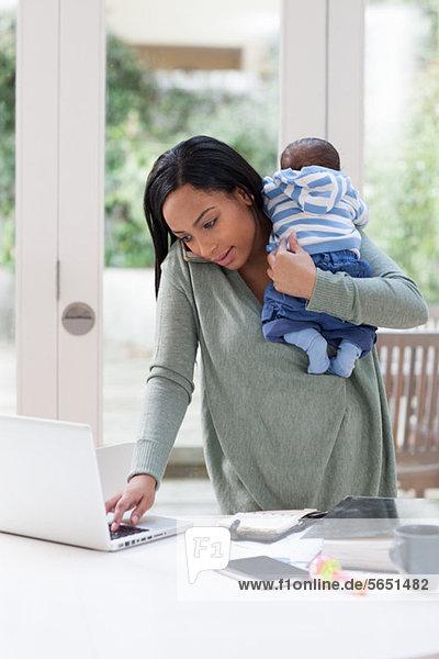 Junge Frau mit Baby und Laptop