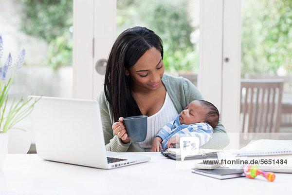 Mutter  die ihren kleinen Sohn hält  mit Laptop und Kaffeetasse