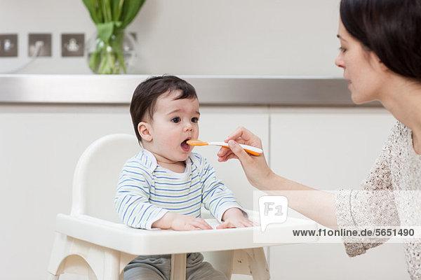 Mutter füttert Kindersohn im Hochstuhl