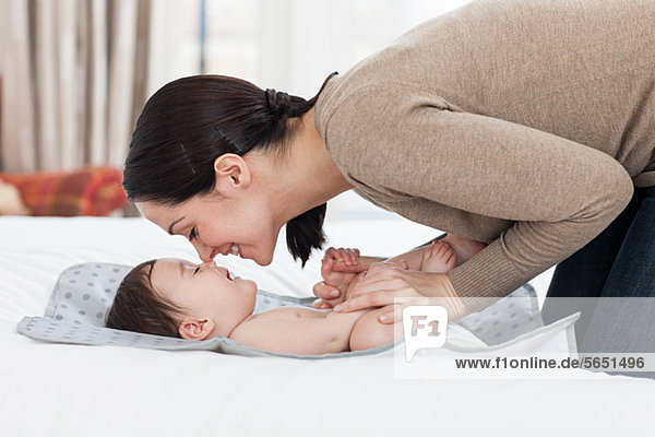 Mother rubbing noses with baby boy on changing mat
