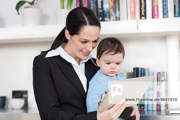 Geschäftsfrau Mutter und Baby beim Betrachten des digitalen Tabletts