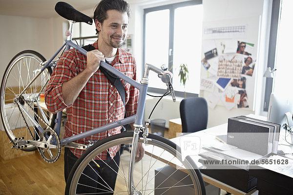 Mittlerer erwachsener Mann mit Fahrrad  lächelnd