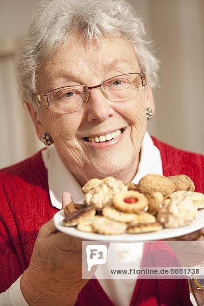 Seniorin mit Weihnachtsplätzchen  lächelnd  Portrait
