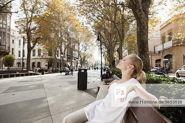 Spanien  Mallorca  Palma  Junge Frau ruht auf Bank