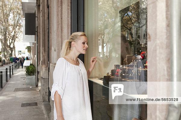 Spanien  Mallorca  Palma  Junge Frau sucht im Schaufenster