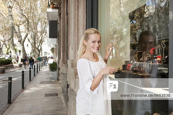 Spain  Mallorca  Palma  Young woman at shop window  smiling  portrait