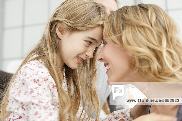 Germany  Leipzig  Mother and daughter looking at each other  smiling