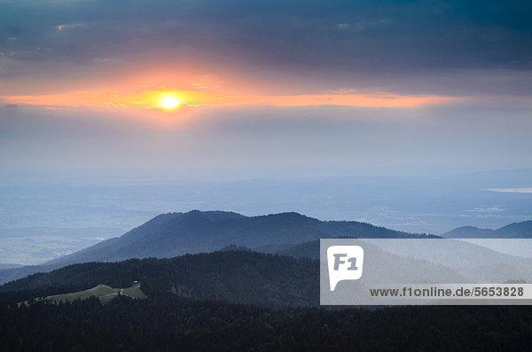Sonnenuntergang zwischen Wolkenbänken  Blick vom Brauneckgipfel Richtung Westen  Bayern  Deutschland  Europa
