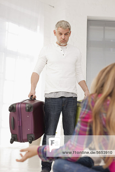 Germany  Leipzig  Father and daughter with packed luggage in apartment