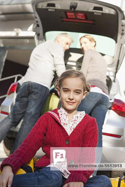 Deutschland  Leipzig  Familie beim Verladen von Gepäck ins Auto  lächelnd