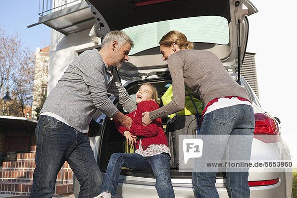 Deutschland  Leipzig  Familie beim Verladen von Gepäck ins Auto
