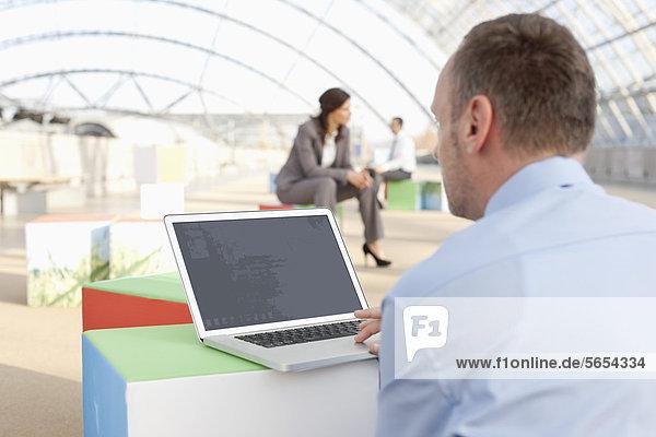 Deutschland  Leipzig  Geschäftsmann mit Laptop  Geschäftsleute im Hintergrund