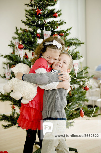 Brother and sister hugging in front of a Christmas tree