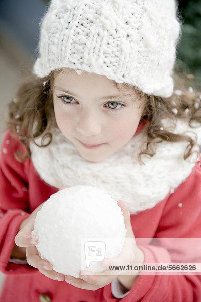 Mädchen mit Winterkleidung hält Schneeball