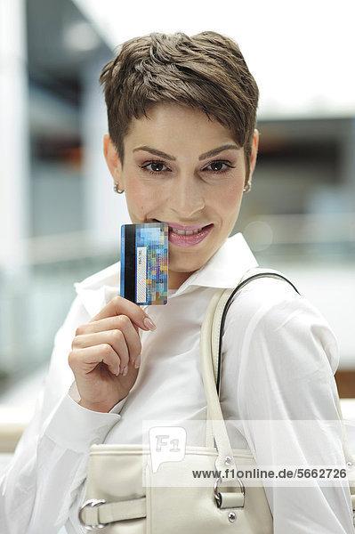 Junge Geschäftsfrau mit Kreditkarte
