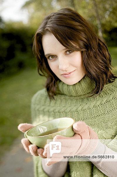 Junge Frau hält eine Tasse Tee