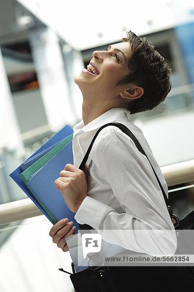 Lachende junge Geschäftsfrau mit Dokumentenmappen