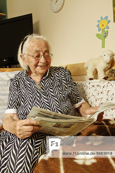 Alte Frau liest Zeitung im Pflegeheim