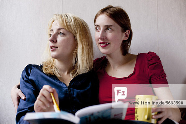 Two female friends with book and cup looking away over colored background