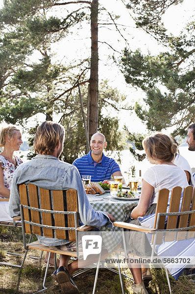 Gruppe von Freunden beim gemeinsamen Essen im Freien