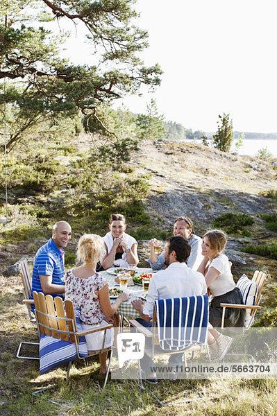 Freunde  die im Freien zusammen essen.
