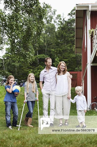 Familie mit drei Kindern  die im Hinterhof stehen.