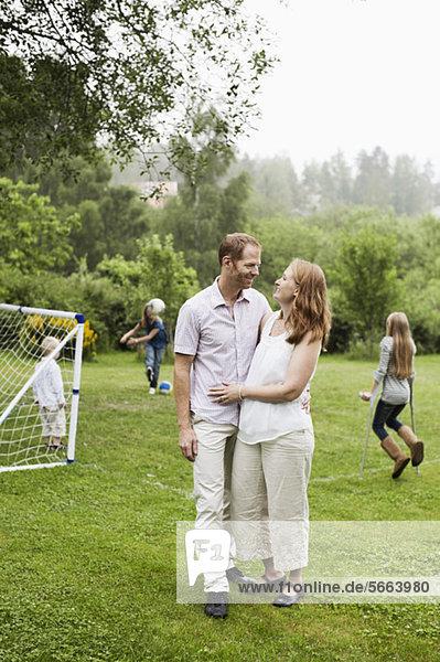 Ein Paar schaut sich an  während die Kinder im Hintergrund spielen.