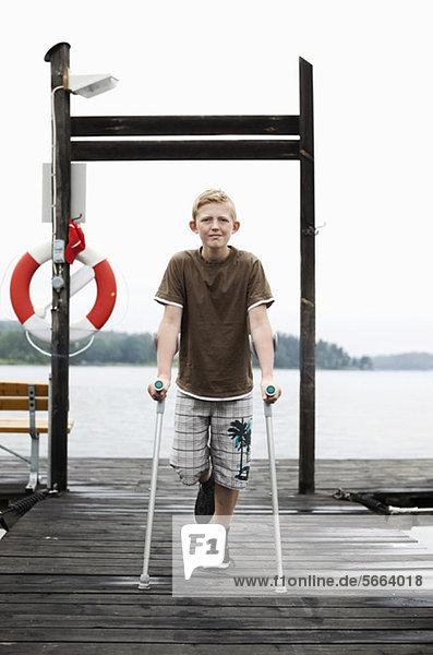 Portrait eines Jungen mit Krücken im Stehen auf einem Bein