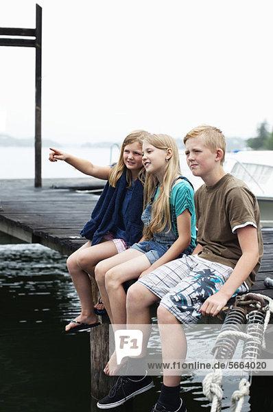 Bruder und Schwester sitzen Seite an Seite auf dem Pier