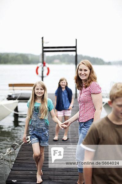 Mutter hält die Hand der Tochter beim Gehen auf dem Pier