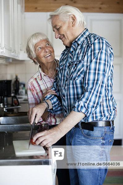 Glückliches Seniorenpaar beim gemeinsamen Kochen