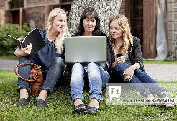 Reife Freundinnen sitzen auf dem Rasen mit Laptop