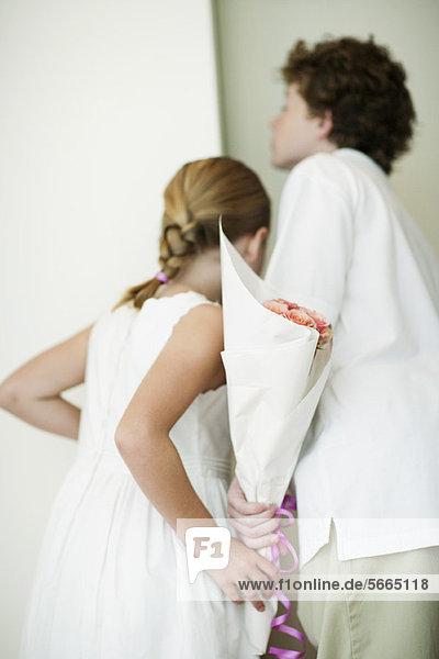 Young siblings holding bouqet of flowers behind backs  peeking through doorway