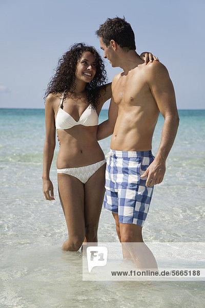 Paar Waten im Wasser am Strand