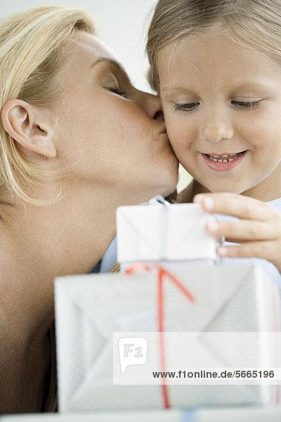 Mutter küsst die Wange der kleinen Tochter  während das Mädchen auf verpackte Geschenke schaut.