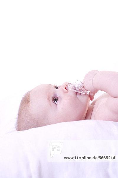 Baby liegend mit Schnuller im Mund