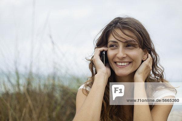 Junge Frau im Gespräch am Handy  Porträt