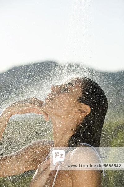 Mittlere Erwachsene Frau beim Duschen im Freien