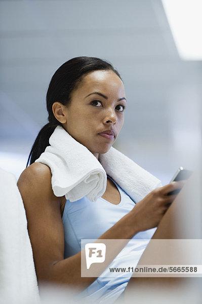 Junge Frau in Sportbekleidung mit dem Handy