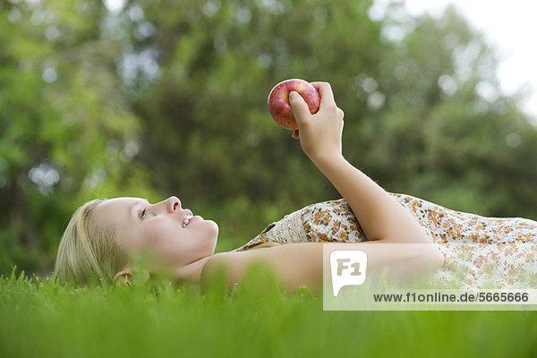 Junge Frau auf Gras liegend  Apfel haltend
