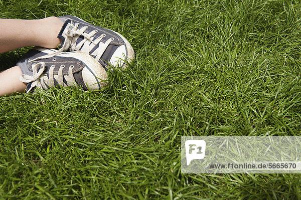 Kinderfüße in Turnschuhen auf Gras  niedriger Schnitt Kinderfüße in Turnschuhen auf Gras, niedriger Schnitt