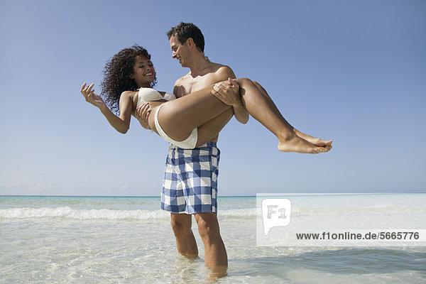 Paar zusammen am Strand  Mann trägt Frau