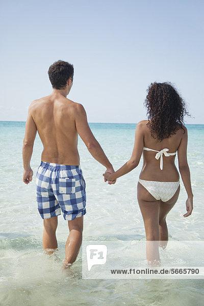 Paar hält Hände beim Waten im Meer  Rückansicht