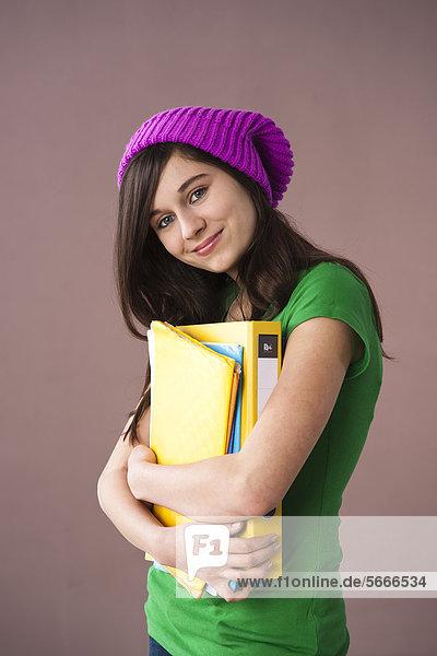 Teenagerin mit Wollmütze hält Mappen