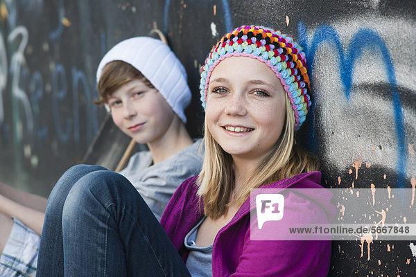 Teeange girl and boy sitting at graffiti wall