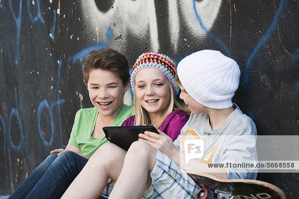 Three teenage friends using tablet PC