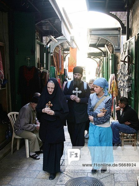 A group holding crosses walks through a market in the old city section of Jerusalem